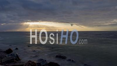 Clouds Passing Over The Sky And Ocean In Time Lapse At Sundown