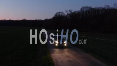 Suv Car Moving Forward On A Straight Road At Night Tracked By Drone